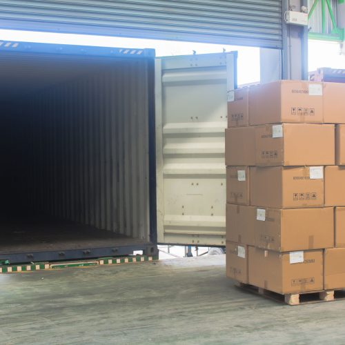 loading shipment carton boxes and goods on wooden pallet at loading dock from container