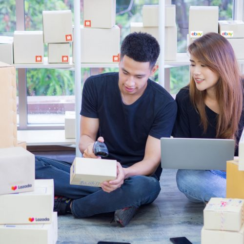 Asian young couple are a new e-commerce entrepreneurs, working as a teamwork and using various technologies internet for the business efficiency whether it is a website and various social media
